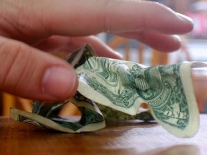 Photo of a hand grabbing money, symbolizing the US government's eminent domain powers