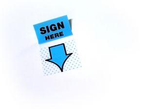 "Photo of a ""Sign Here"" sticker symbolizing an at-will employment offer letter"